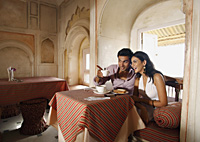 couple sitting at table, man pointing out - Vivek Sharma