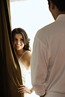 woman smiling at man from behind curtain - Alex Mares-Manton