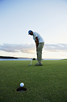 man playing golf during sunset - Yukmin
