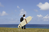 man holding surf board, looking out to sea - Yukmin