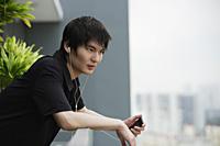 young man listening to MP3, on balcony - Yukmin
