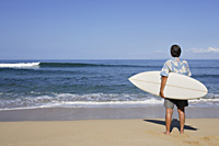 man holding surf board on beach - Yukmin