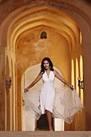 woman walking in arched hallway - Vivek Sharma