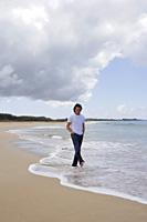 man strolling along shoreline on the beach - Yukmin