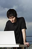 young man standing, using laptop - Yukmin