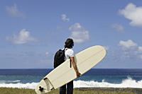 man holding surf board, facing sea - Yukmin