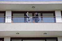 businessmen at balcony shaking hands - Alex Mares-Manton