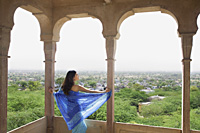 young woman in sari look out from terrace balcony - Alex Mares-Manton
