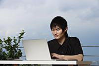 young man sitting outdoor using laptop - Yukmin