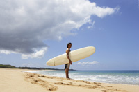 man standing on beach, holding surf board - Yukmin