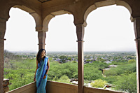 young woman in sari leaning against pillar on terrace balcony - Alex Mares-Manton
