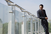businessman leaning against railing on balcony - Alex Mares-Manton