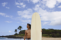 man standing on beach with surfboard - Yukmin