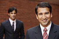 two businessmen, one smiling - Alex Mares-Manton