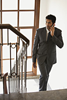 businessman on phone, walking up stairs - Alex Mares-Manton