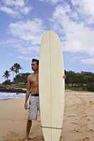 man standing on beach with surf board - Yukmin