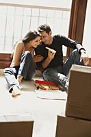 young couple having pizza on floor - Alex Mares-Manton