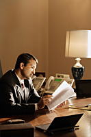 businessman reading documents in office - Alex Mares-Manton