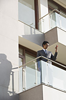 businessman with mobile phone standing on balcony - Alex Mares-Manton