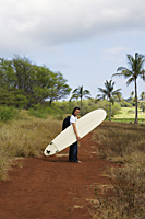 man walking on trail with surf board - Yukmin