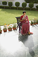 woman wearing a sari, knitting - Alex Mares-Manton