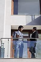 business associates speaking on balcony - Alex Mares-Manton