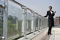 business woman standing on balcony - Alex Mares-Manton