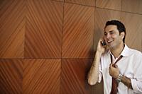 businessman on cell phone, loosening tie - Alex Mares-Manton