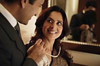 man putting string of pearls around woman's neck - Alex Mares-Manton