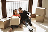 young couple in new home with moving boxes - Alex Mares-Manton