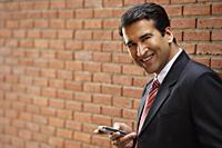 businessman leaning against wall - Alex Mares-Manton