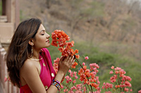 young woman in sari, smelling flowers - Alex Mares-Manton