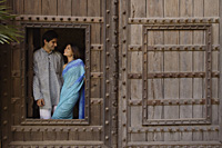 young couple at window in huge wooden doorway - Alex Mares-Manton