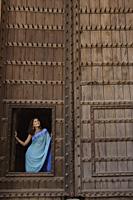 young woman standing at opening of huge wooden doorway - Alex Mares-Manton