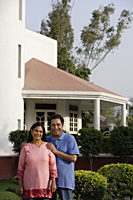 smiling couple standing in front of house - Alex Mares-Manton