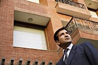 man in suit, standing in front of home - Alex Mares-Manton