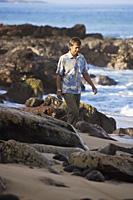 mature man walking along rocky beach - Yukmin