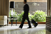businessman walking through hotel lobby - Alex Mares-Manton