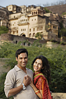 smiling young couple standing with palace in background - Alex Mares-Manton