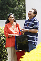 couple laughing with shopping bags - Alex Mares-Manton