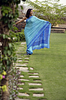 young woman wearing sari walking in garden, arms stretch out - Alex Mares-Manton