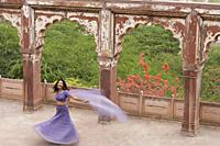 young woman in sari, dancing on terrace - Alex Mares-Manton