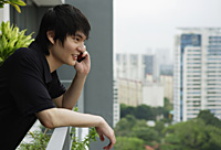 young man standing at balcony, using mobile phone - Yukmin