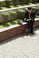 businessman working on laptop outside - Alex Mares-Manton