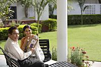 couple sitting outside, holding photograph - Alex Mares-Manton
