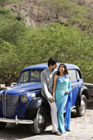 young couple looking at each other in front of blue antique car - Alex Mares-Manton