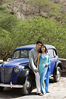 young couple standing in front of blue antique car - Alex Mares-Manton