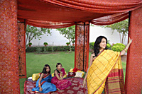 three young women wearing saris, in red tent - Alex Mares-Manton