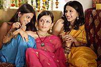 three young women wearing saris, one with bindi - Alex Mares-Manton