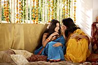 two young women gossiping, wearing saris - Alex Mares-Manton